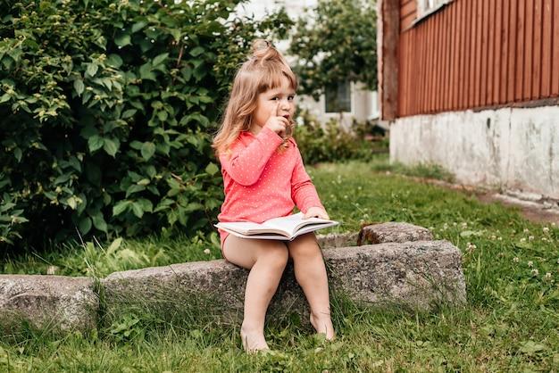 Babymeisje in een rood op groen gras en het lezen van een boek op een zonnige zomerdag.
