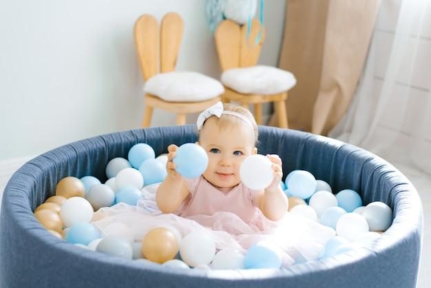 Babymeisje in een roze jurk, zittend in een zwembad met ballen