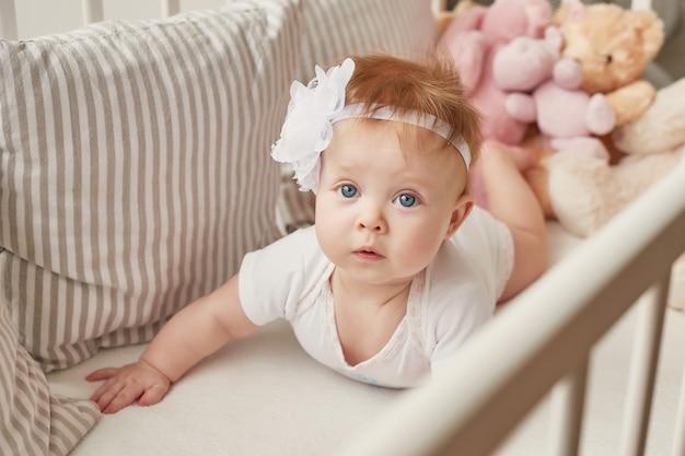 Babymeisje in een wieg met speelgoed in de kinderkamer