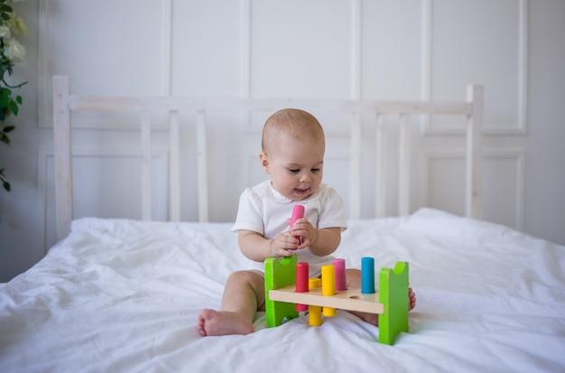 Babymeisje in een witte bodysuit speelt met educatief speelgoed op het bed
