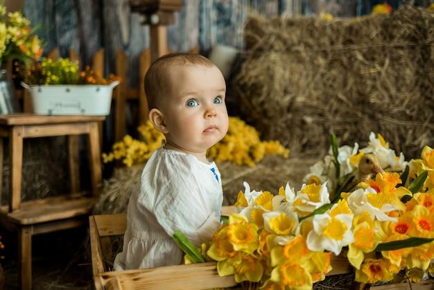 Babymeisje in een witte linnen jurk met borduurwerk zit in een houten kar met bloemen in de schuur
