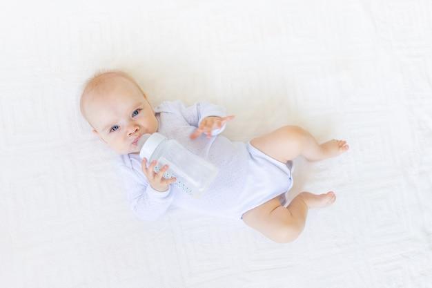 Babymeisje in een witte romper liggend op haar rug op een wit bed thuis met een fles water