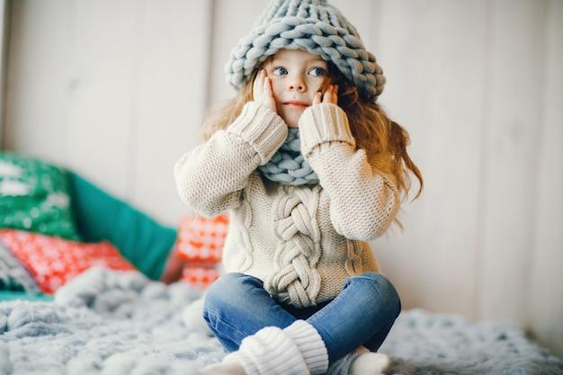 Babymeisje in gebreide muts en sjaal