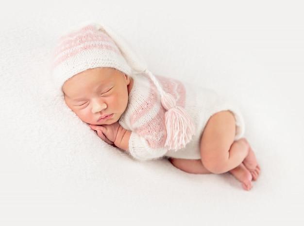 Babymeisje in gebreide pak en hoed