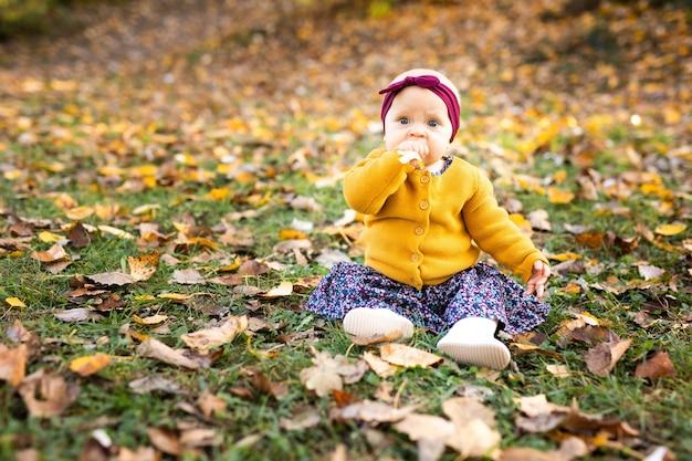 Babymeisje in geel jasje en rode hoofdband zitplaatsen op het gras, spelen in de herfstbladeren.