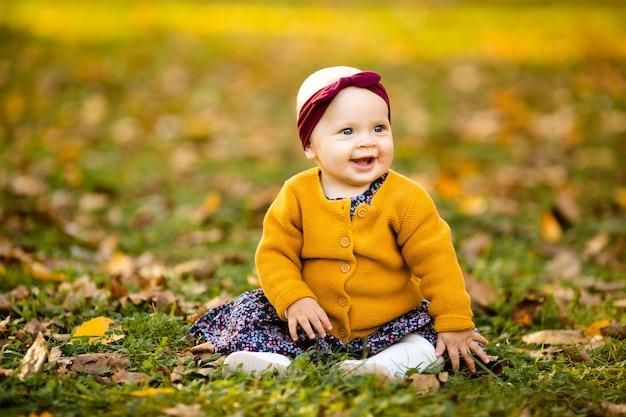 Babymeisje in geel jasje en rode hoofdbandplaatsing op het gras