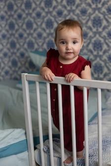 Babymeisje in het rood staat aan de leuning van haar bed en kijkt naar de camera. blauwe en witte achtergrond. verticale oriëntatie