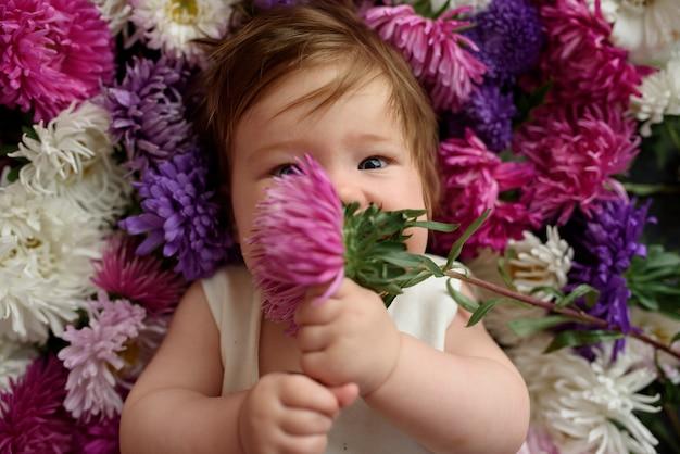 Babymeisje in het witte kleding spelen met bos van bloemen