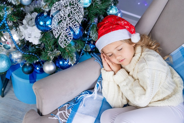 Babymeisje in kerstmuts slapen in de buurt van de kerstboom, het concept van nieuwjaar en kerstmis
