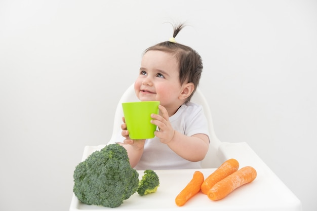 Babymeisje in kinderstoel drinkwater uit beker.