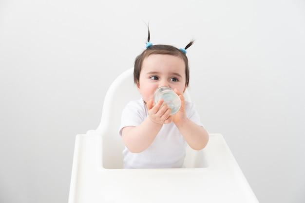 Babymeisje in kinderstoel drinkwater uit de zuigfles.