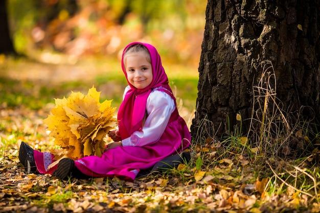 Babymeisje in kostuums van masha uit cartoon masha and bear op herfstbos