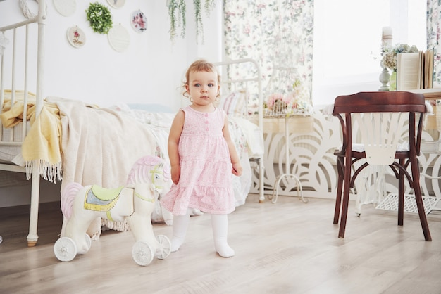 Babymeisje in leuke kleding die bij bed het spelen met speelgoed door het huis situeren. witte vintage kinderkamer. jeugd concept