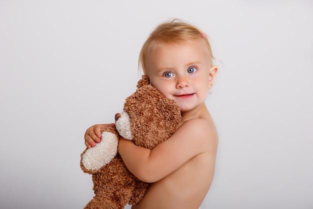 Babymeisje in luier het spelen met teddybeer op wit.