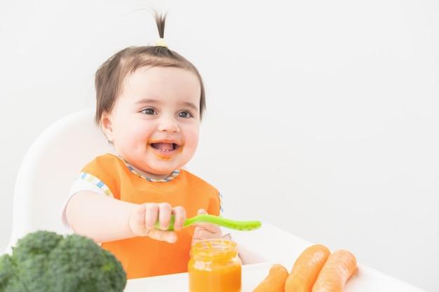 Babymeisje in oranje slabbetje zittend in een stoel childs plantaardige puree eten.