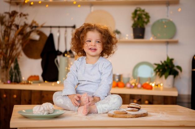 Babymeisje in pyjama's in de keuken