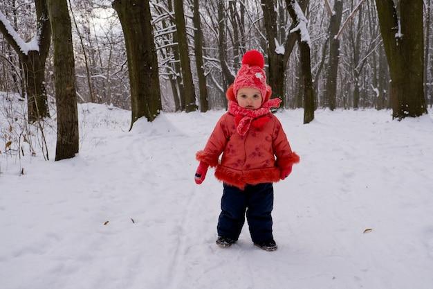 Babymeisje in rode jas wandelen door sneeuw in het bos.