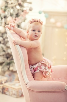 Babymeisje in roze kleding en gelukkig interieur in retro stijl Premium Foto