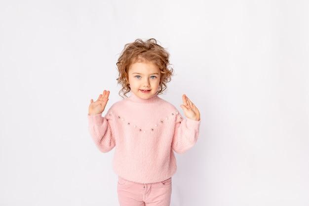 Babymeisje in roze winterkleren op witte achtergrond verheugt zich, ruimte voor tekst
