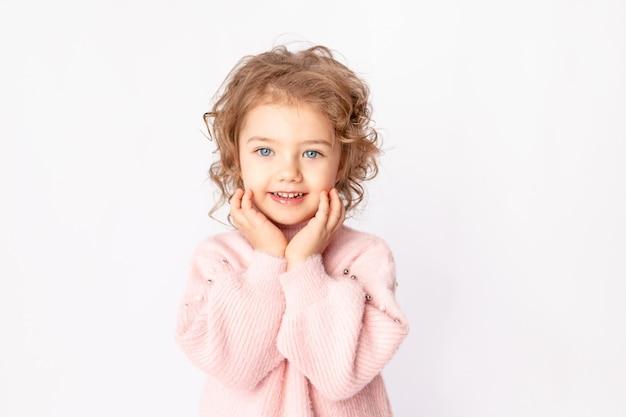 Babymeisje in roze winterkleren op witte achtergrond