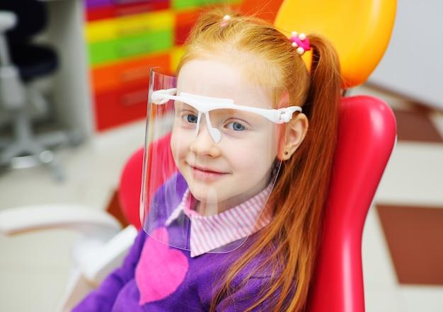 Babymeisje in tandbril het glimlachen zitting als tandvoorzitter.