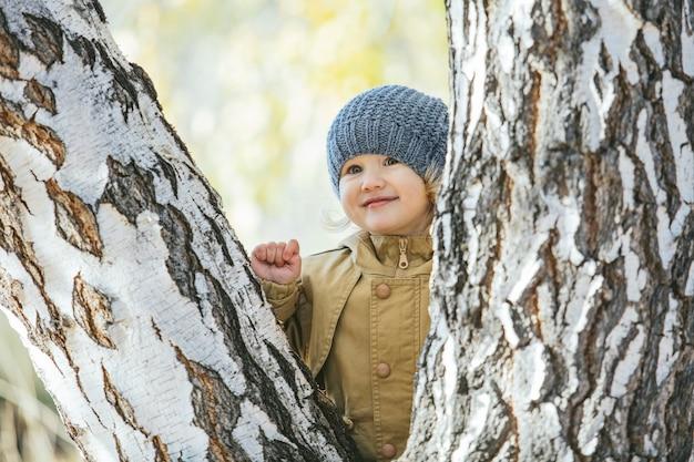 Babymeisje in warme jas en muts in de herfst in het park