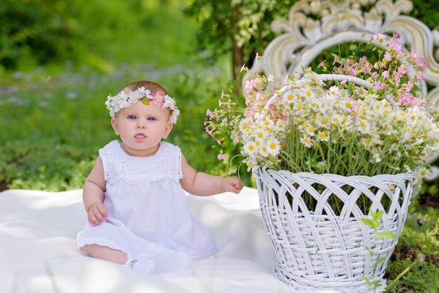 Babymeisje in witte kleding in een de lentetuin met bloemen