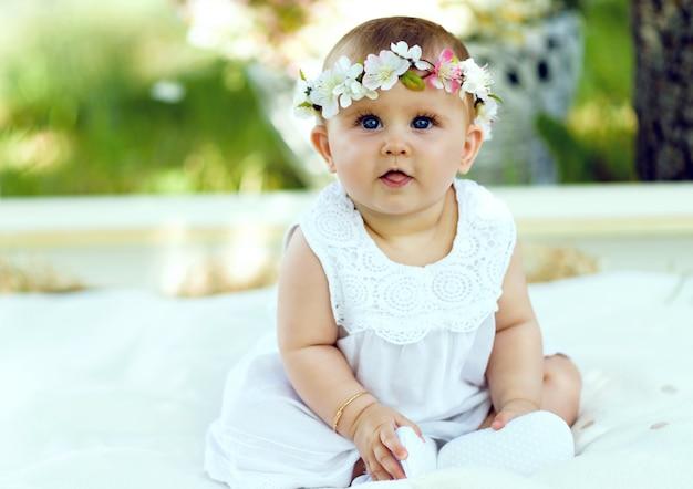 Babymeisje in witte kleding in een de lentetuin met bloemkroon