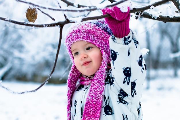Babymeisje in witte snowsuite en roze hoed, laarzen en handschoenen in het park van de sneeuwwinter.