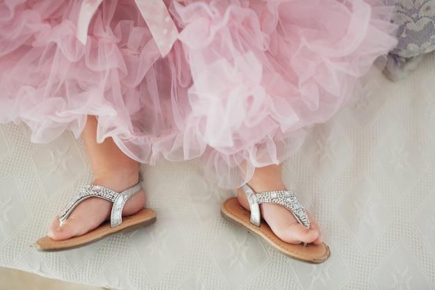 Babymeisje in zilveren schoenen en mooie roze jurk