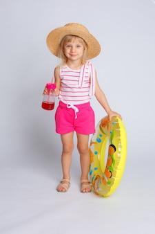 Babymeisje in zomer kleding en zwemmen cirkel met sap in haar handen. het concept van de zomervakantie