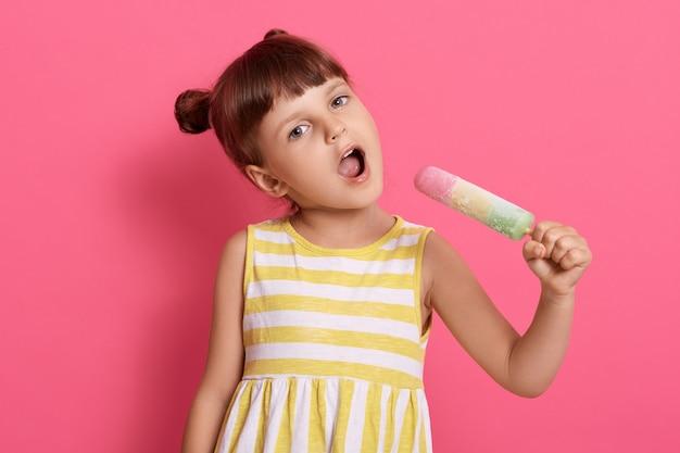 Babymeisje kind houdt groot ijs als microfoon en zingt, vrouwelijk kind stelt zich voor dat ze zangeres en zingt met waterijs in handen op roze muur.
