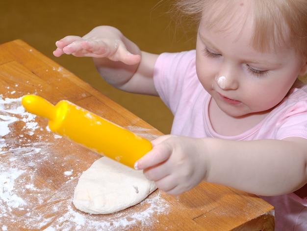 Babymeisje kneedt het deeg op een tafel met handen en een deegroller