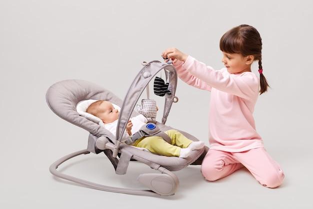 Babymeisje liggend in wieg met haar zus