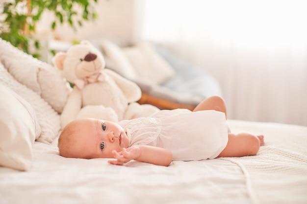 Babymeisje liggend op haar rug op het bed in een lichte slaapkamer, gekleed in een lichte zomerjurk. kalme baby baby 3 maanden oud.