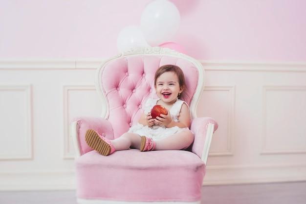 Babymeisje met appel in roze interieur met vintage stoel en ballonnen