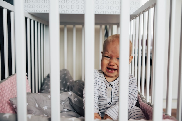 Babymeisje met blauwe ogen en blond haar huilt in haar bed