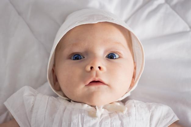 Babymeisje met blauwe ogen in witte jurk en hoed op witte deken.