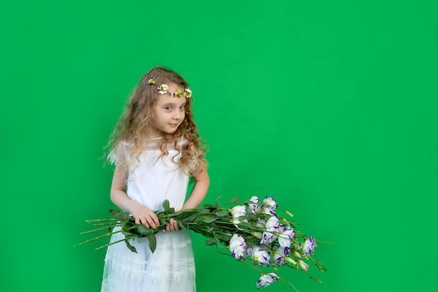 Babymeisje met bloemen op een groene achtergrond