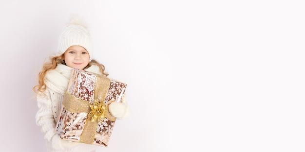 Babymeisje met cadeau in warme muts en trui op witte geïsoleerde achtergrond, plaats voor tekst, banner Premium Foto