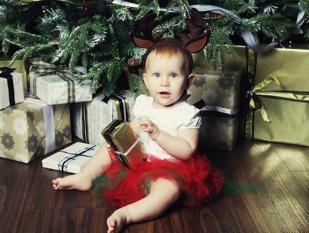 Babymeisje met de geschenkdoos in de buurt van kerstboom versieren. vrolijke tijd.