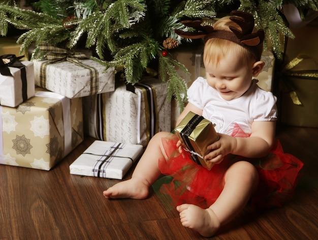 Babymeisje met de geschenkdoos in de buurt van kerstboom versieren