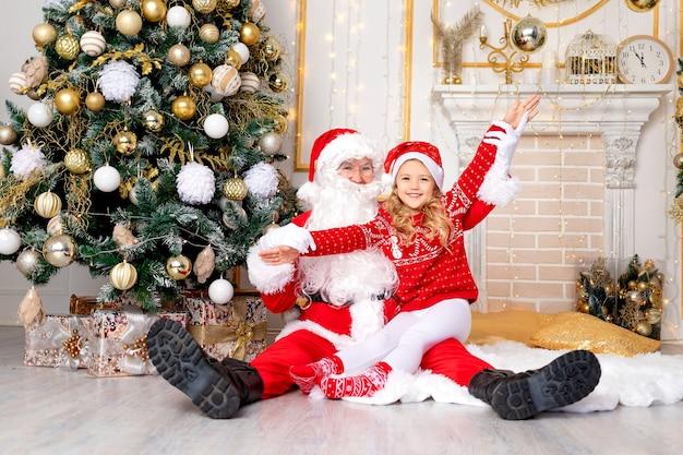 Babymeisje met de kerstman bij de kerstboom, het nieuwe jaar en het kerstconcept
