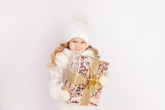 Babymeisje met een cadeau in een warme muts en trui op een witte geïsoleerde achtergrond, ruimte voor tekst