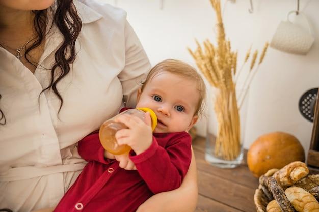 Babymeisje met een fles appelsap