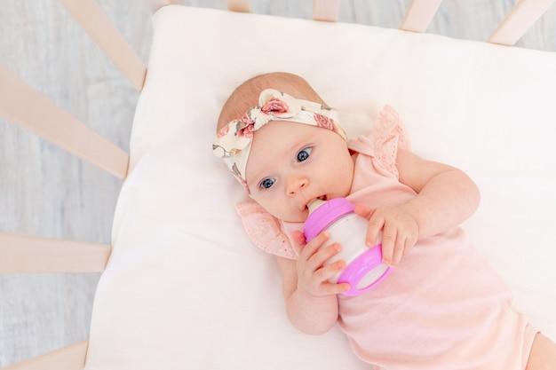 Babymeisje met een fles melk in haar handen op een wit katoenen bed thuis, het concept gezonde voeding voor kinderen