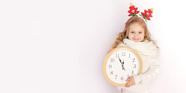 Babymeisje met een klok op een witte geïsoleerde achtergrond met de trui, plaats voor tekst, concept van nieuwjaar en kerstbanner