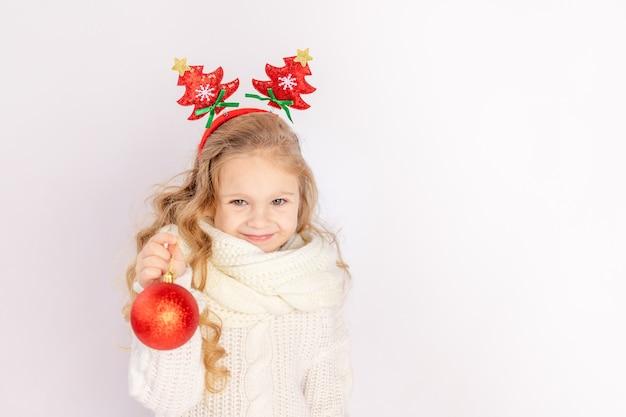 Babymeisje met een rode kerstbal op een witte geïsoleerde achtergrond, ruimte voor tekst