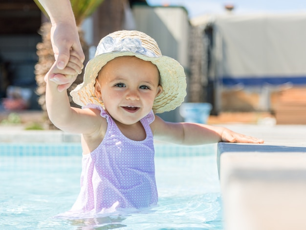 Babymeisje met hoed in zwembad en moeder.