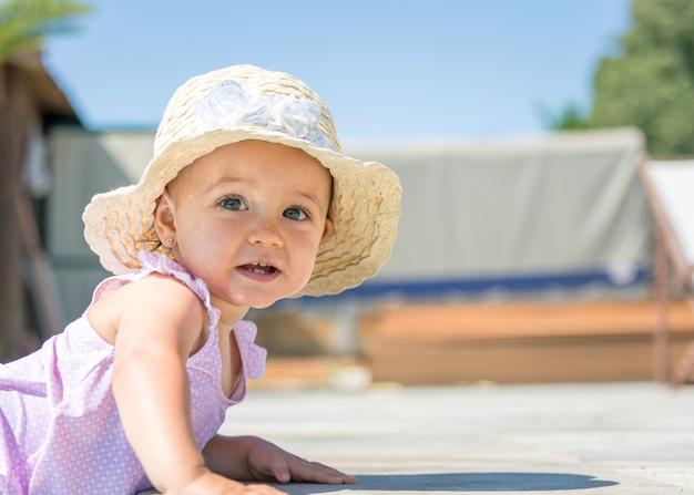 Babymeisje met hoedenglimlach in zwembad.